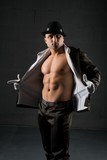Young muscular man in a hat and unbuttoned shirt - 240699316
