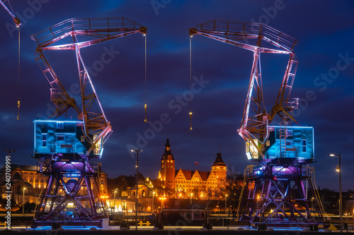 Foto Murales Illuminated old port cranes on a boulevard in Szczecin City at night