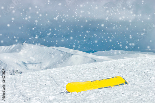 obraz lub plakat snowboard on the snow against the backdrop of the beautiful snow-capped mountains