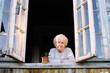 Elderly woman looks from window of a village house.