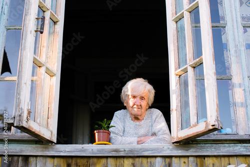 Foto Murales Elderly woman looks from window of a village house.