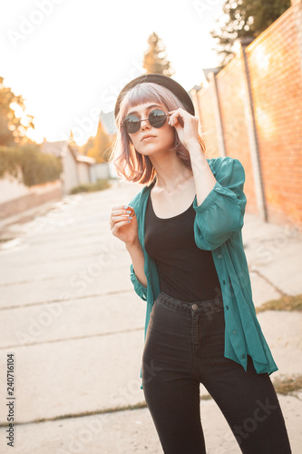 mata magnetyczna Young woman with sunglasses and hat is walking along the street at sunset