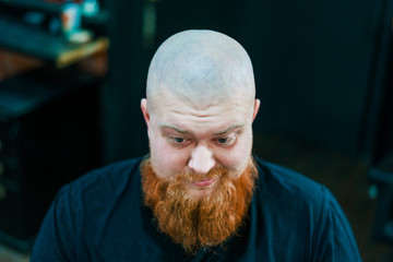 Thoughtful man with red beard is smirking and looking down. © stockaboo