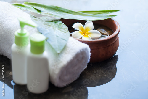 Bbowl of water, towel and cream tubes. Body care and spa concept on black background