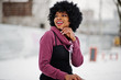Curly hair african american woman posed at winter day, sitting on bench.
