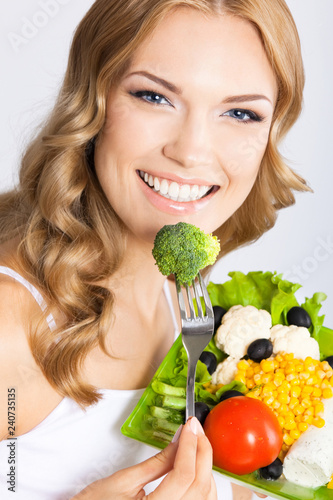 Foto Murales Woman with vegetarian salad, over gray