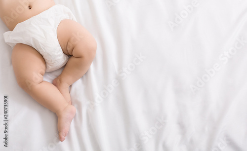 Baby legs and bottom in diaper on bed