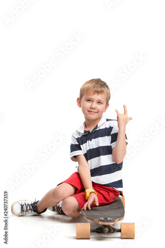 Full length portrait of an adorable young boy riding a skateboard isolated against white background at studio