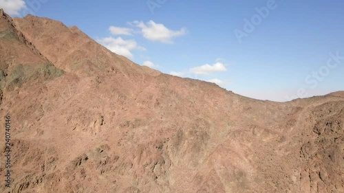 Desert landscape - Aerial footage of mountains and dry land with blue cloudy sky in the background.