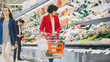 Leinwanddruck Bild - At the Supermarket: Beautiful Young Woman Walks Through Fresh Produce Section, Chooses Vegetables. Customer Shopping for Fruits and Vegetables at the Store.