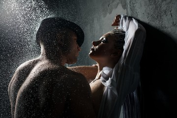 Young couple embracing in shower in the dark
