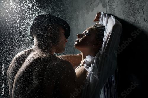Leinwandbild Motiv Young couple embracing in shower in the dark
