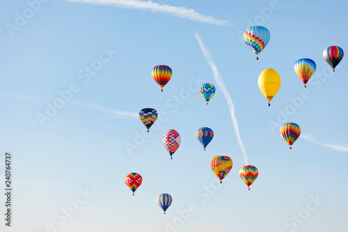 Multi colored hot air balloon flying over blue sky