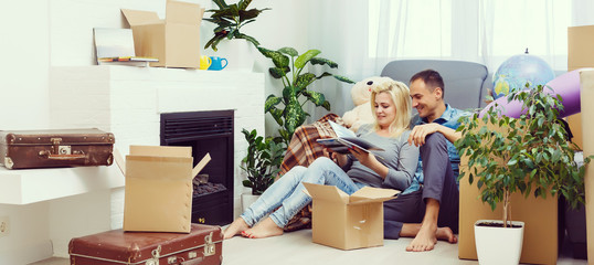 Young couple moving in new home.Sitting on floor and relaxing after cleaning and unpacking © Angelov