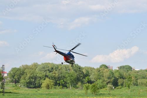 гражданский вертолет взлетает с поля в городе