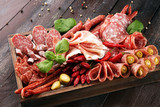 Food tray with delicious salami, pieces of sliced prosciutto crudo, sausage and basil. Meat platter with selection - 240773370