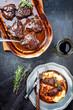 Leinwanddruck Bild - Traditionelle deutsche geschmorte Kalbsbäckchen in brauner Rotwein Sauce mit Kartoffelpüree als Draufsicht auf einem Zinnteller