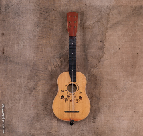 old guitar on dirty brown background - 240776180