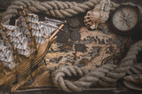 Pirate ship, treasure map, compass and a mooring rope on a wooden table background.