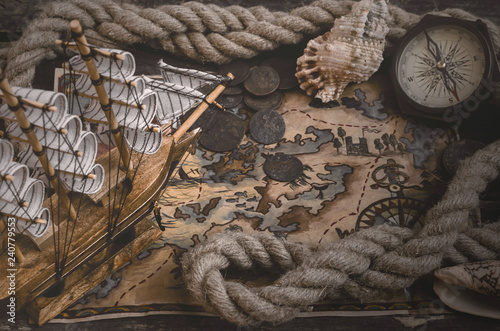 Leinwanddruck Bild Pirate ship, treasure map, compass and a mooring rope on a wooden table background.