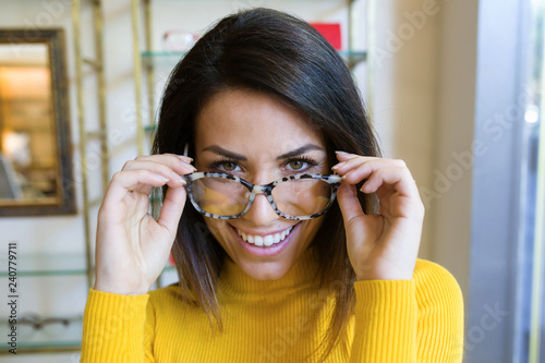 Beautiful young woman showing her new eyeglasses while looking at camera in optic shop.