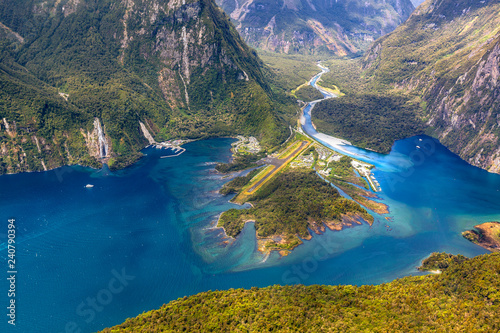 New Zealand. Milford Sound (Piopiotahi) from above - the head of the fiord with wharf and Milford Sound Airport. There is Cleddau River in the background - 240790394