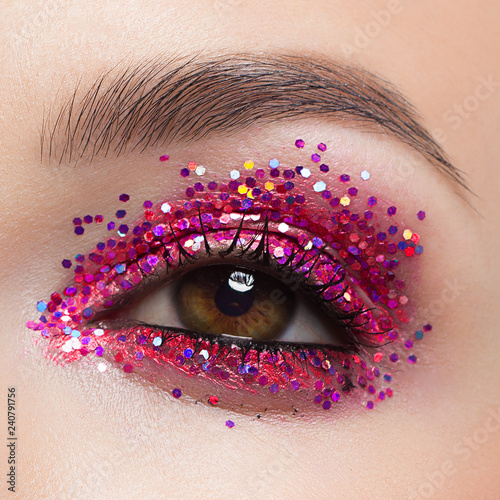 Close eye with colorful eyeshadow. Macro shot of opened human female eye. Woman with evening beauty makeup. Girl with perfect skin and eyebrow. Women cosmetics, extremely long eyelash and red glitter - 240791756