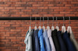 Leinwanddruck Bild - Wardrobe rack with stylish clothes near brick wall. Space for text