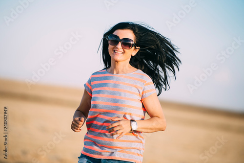 Beautiful brunette woman with sunglasses posing in the summer field.