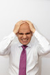Angry bald man with hands on his head