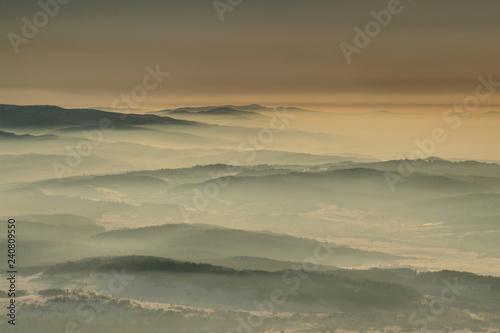 Aerial view of gentle slopes in winter haze at dawn in Gorce, Beskid Sadecki and Zywiecki ranges from Babia Gora peak, Beskidy Zachodnie mountains Western Carpathians Podhale Malopolska Poland Europe