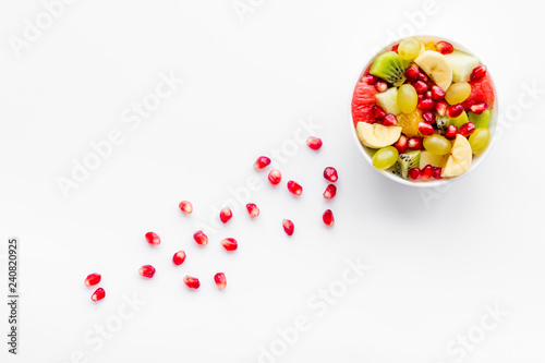 Fruit diet concept. Fruit salad with apple, kiwi and pomegranate in bowl on white background top view copy space - 240820925