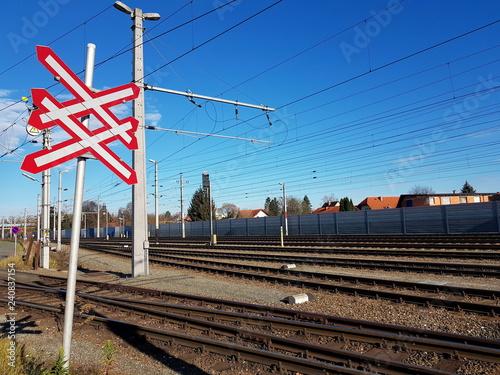 Eisenbahn: Gleise und Andreaskreuz vor einem Bahnhof