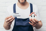 cropped image of male craftsman showing house model and card with lettering home inspection - 240858531