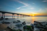 Bridge on the beach at sunrise
