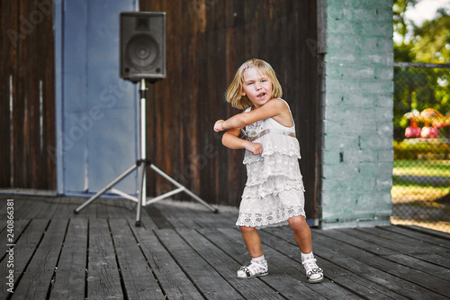 Little girl in white dress dancing outdoors at the old wooden stage - 240866381