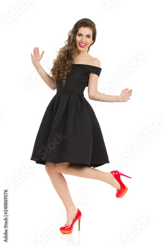 Excited Elegant Woman In Black Dress Is Dancing On One Leg - 240869576
