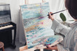 artist holding palette and painting on canvas at home