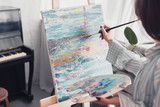 artist holding palette and painting on canvas at home - 240874389