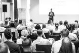 Speaker giving a talk in conference hall at business event. Focus on unrecognizable people in audience. Business and Entrepreneurship concept. Black and white image. © kasto