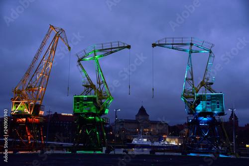 Zdjęcia na płótnie, fototapety na wymiar, obrazy na ścianę : Colorfully illuminated antique cranes on the quay of Szczecin Łasztownia.