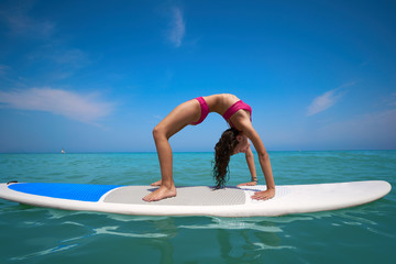 Girl gymnastics on paddle surf board SUP