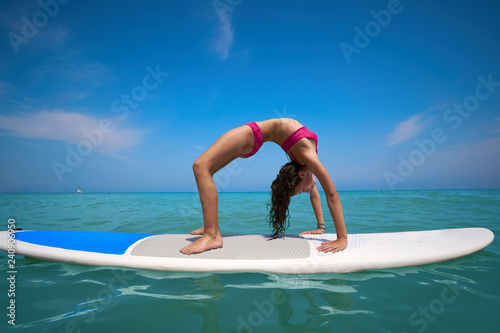 Leinwanddruck Bild Girl gymnastics on paddle surf board SUP