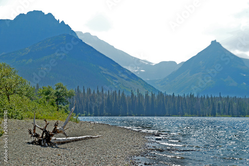 Clear lake water surrounded with mountains in Glacier National Park.