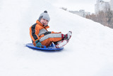 Happy laughing small boy slides down the hill on snow saucer. Seasonal concept. Winter day. - 240941146