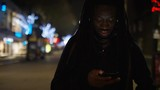 Young black male with dreadlocks using his phone out in the high street at night - 240962377