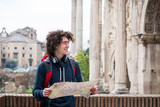 Handsome tourist holding a tourist map near Roman forum in Rome, Italy. - 240962537