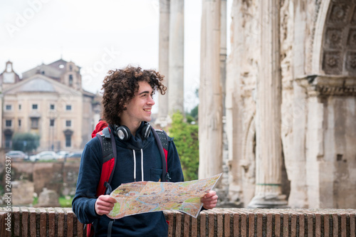 Sticker Handsome tourist holding a tourist map near Roman forum in Rome, Italy.