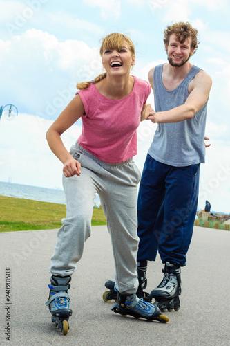 Woman encourage man to do rollerblading - 240981503