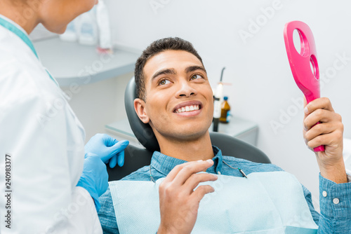 handsome african american man smiling and looking at mirror